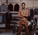African-American man dressed in a trendy elegant suit posing with crossed arms near retro sports motorbike at the men's clothing store. - 229629600