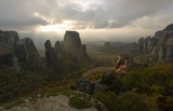 The valley of Meteora with monasteries built on top of rocky cliffs in golden light