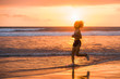 Leinwanddruck Bild - silhouette of fit and athletic Asian Chinese sporty woman running on beautiful beach doing jogging workout on sunset in fitness healthy lifestyle and summer outdoors activity