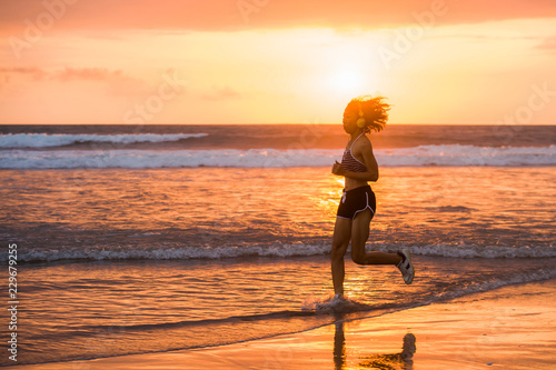 Leinwanddruck Bild silhouette of fit and athletic Asian Chinese sporty woman running on beautiful beach doing jogging workout on sunset in fitness healthy lifestyle and summer outdoors activity