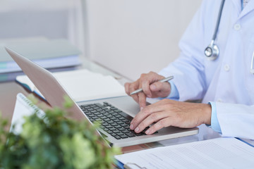 Cropped image of general practitioner working on laptop at her table