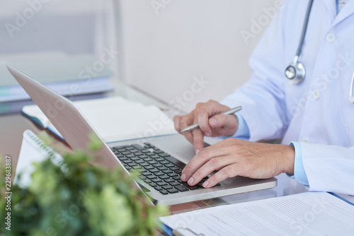Cropped image of general practitioner working on laptop at her table © DragonImages