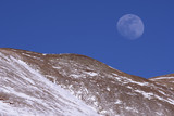 Moon rises over Hoosier Ridge and Red Mountain near dusk sunset in the Rocky Mountains, Colorado