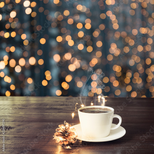 Poster Cup of black coffee on wooden table in cafe. Blurred gold garland as background. Christmas Time. Image for display or montage your products.