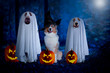 Leinwanddruck Bild - Halloween, three dogs sit disguised as ghost and witch in front of pumpkins