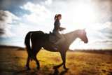 beautiful girl riding a black horse on a Sunny day. equestrian sport - 229701049