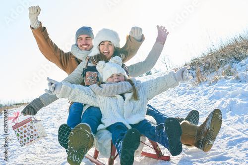 Leinwanddruck Bild Familie hat Spaß beim Schlitten fahren