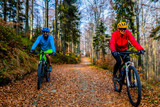 Cycling, mountain biker couple on cycle trail in autumn forest. Mountain biking in autumn landscape forest. Man and woman cycling MTB flow uphill trail. - 229702803