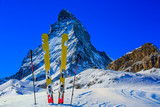 Ski in winter season, mountains and ski touring backcountry equipments on the top of snowy mountains in sunny day with Matterhorn in background, Zermatt in Swiss Alps. - 229704887
