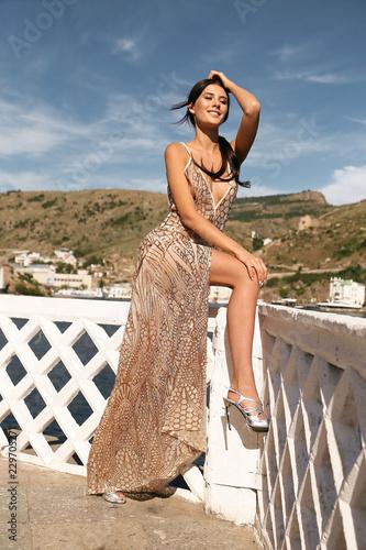 e0e293606b5 beautiful woman with dark hair in luxurious dress walking near the ...