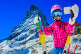 Teenager taking a selfie, girl taking a self portrait with mobile phone, sport skiing having fun on winter vacation with Matterhorn in background, Zermatt. - 229705884