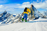 Man skiing on fresh powder snow. Ski in winter season, mountains and ski touring backcountry equipments on the top of snowy mountains in sunny day with Matterhorn in background, Zermatt in Swiss Alps. - 229706419
