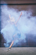 young contemporary dancer dancing in blue smoke on street