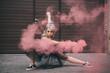 beautiful girl dancing in pink smoke and looking at camera on street