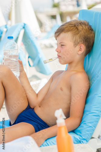 Leinwandbild Motiv Sad little boy on hot beach with sunstroke measures the temperature and holds a bottle of water