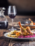 Portion of roast duck leg red cabbage homemade dumplings on plate and red wine on the background - 229718688