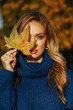 beautiful woman with blond hair in elegant outfit posing in autumn park