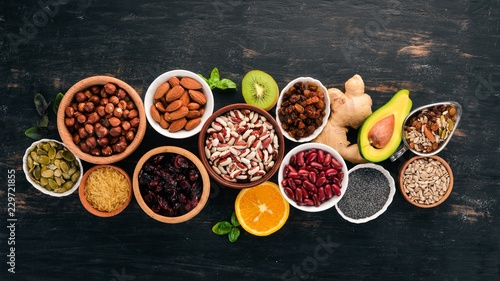 Poster Various superfoods. Dried fruits, nuts, beans, fruits and vegetables. On a black wooden background. Top view. Free copy space.