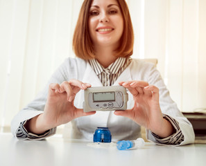Doctor holding the insulin pump at his hands.