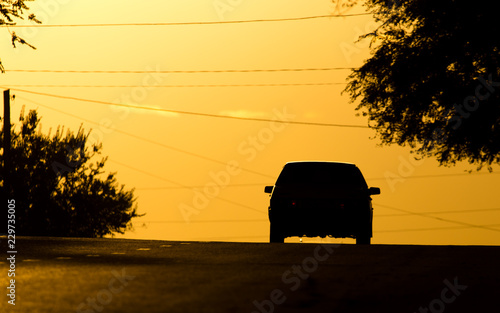 car rides on the road at sunset - 229735005