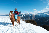 extreme snowboarder. Free rider A man in a cowboy hat riding a horse in the snow. Winter. the mountains. - 229735459