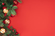 flat lay with pine tree branches with red and golden christmas balls isolated on red