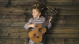 Overhead happy child girl on vintage wooden background playing ukulele guitar.Text or logo copy space.Vertical top view.Social card for Christmas holiday season.4k video - 229739467