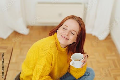 Young woman enjoying a cup of tea - 229739416
