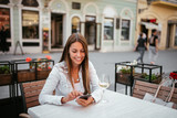 Beautiful young brunette using phone while sitting in outdoors restaurant. - 229746202
