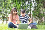 Couple of teenagersoutdoor using laptop on the grass - 229756616