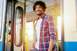 Young beautiful Afro-American man standing on door of public transport. Looking away and going out.