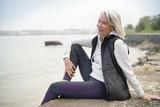 Beautiful elderly woman sitting by the ocean in sportswear - 229776238