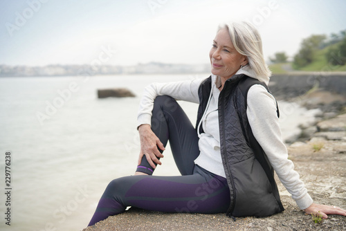 Leinwanddruck Bild  Beautiful elderly woman sitting by the ocean in sportswear