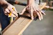 Hände beim Maßanzeichnen mit Bleistift und Liniel auf Holz