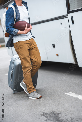 cropped image of man with backpack and rugby ball carrying bag on wheels near travel bus at street - 229789066