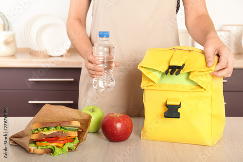 Leinwandbild Motiv Woman packing food for her child at table in kitchen, closeup. Healthy school lunch