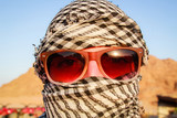 Desert in Egypt. Sharm el Sheikh. Sand and Sand Borkhan. Rock and sunset. Girl in dark glasses in a traditional Arab headgear in a cell - 229792616