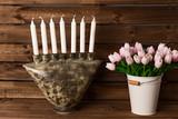 Tulipanes y candelabro de cerámica sobre fondo de madera.