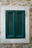 One window with closed green shutters on the background of beige wall.