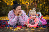 Portrait of mother and little daughter in autumnal scenery - 229816685