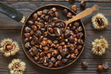 Roasted chestnuts in a pan and whole fruits - 229818253