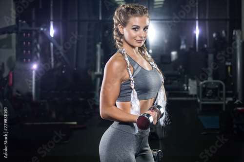 Beautiful young girl blonde, athlete bodybuilder, does exercises with dumbbells. In the modern gym, in beautiful sportswear. The concept is strength, beauty, diet, sports nutrition, sportswear, health - 229831030