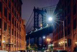 Brooklyn bridge seen from a narrow alley enclosed by two brick buildings at dusk, NYC USA - 229844865