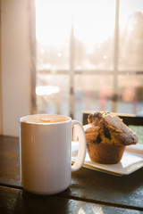 A blueberry muffin and a cup of coffee latte on a wood table with rays sunlight.