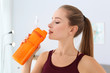 Leinwanddruck Bild - Young woman drinking protein shake at home, closeup view