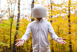 Man dressed in white has a reversed crystal bowl on his head while showing openness - Pictured in the forest while automn colors are at their best in Quebec, Canada