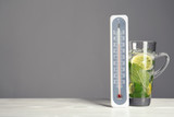 Thermometer and cup of mojito on wooden table against grey background. Space for text