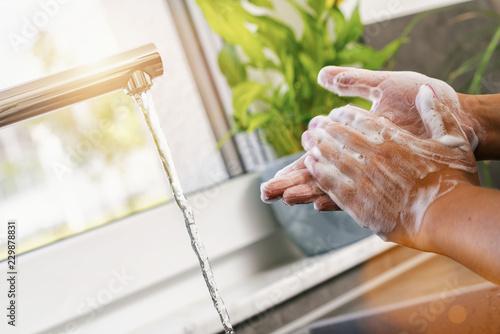Leinwandbild Motiv Woman washing of hands with soap under running water in the kitchen