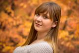 Teenage girl portrait in autumnal scenery - 229887644
