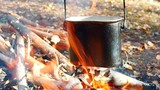 Camping pot on the fire. Extreme tourism in the wild forest.  - 229888637
